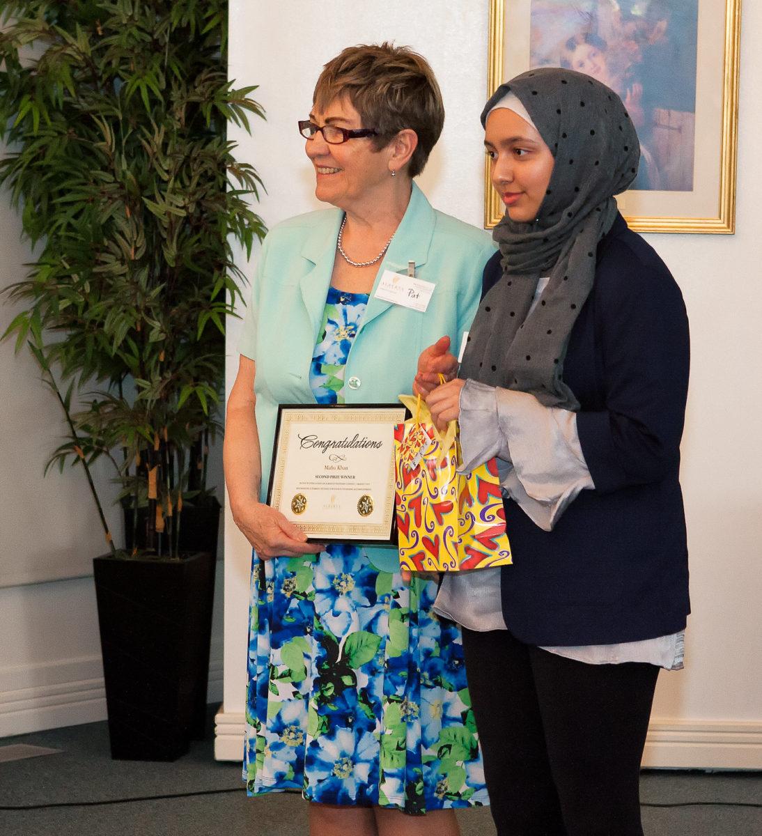 Maha Khan receiving Grade 7-9 Second Prize and plaque